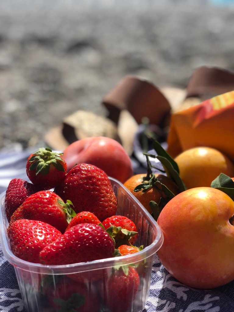 a beach picnic in the amalfi coast of italy including fresh strawberries, plums, and potato chips with dolce vita sandals in the background