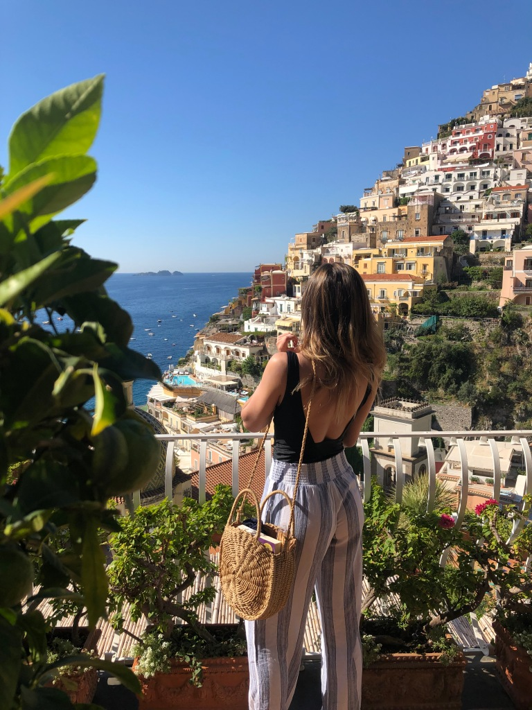 young woman looking out towards the view from la sirenuse in positano italy