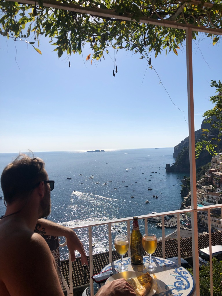 a young male eating pizza on a terrace looking out the view of positano italy
