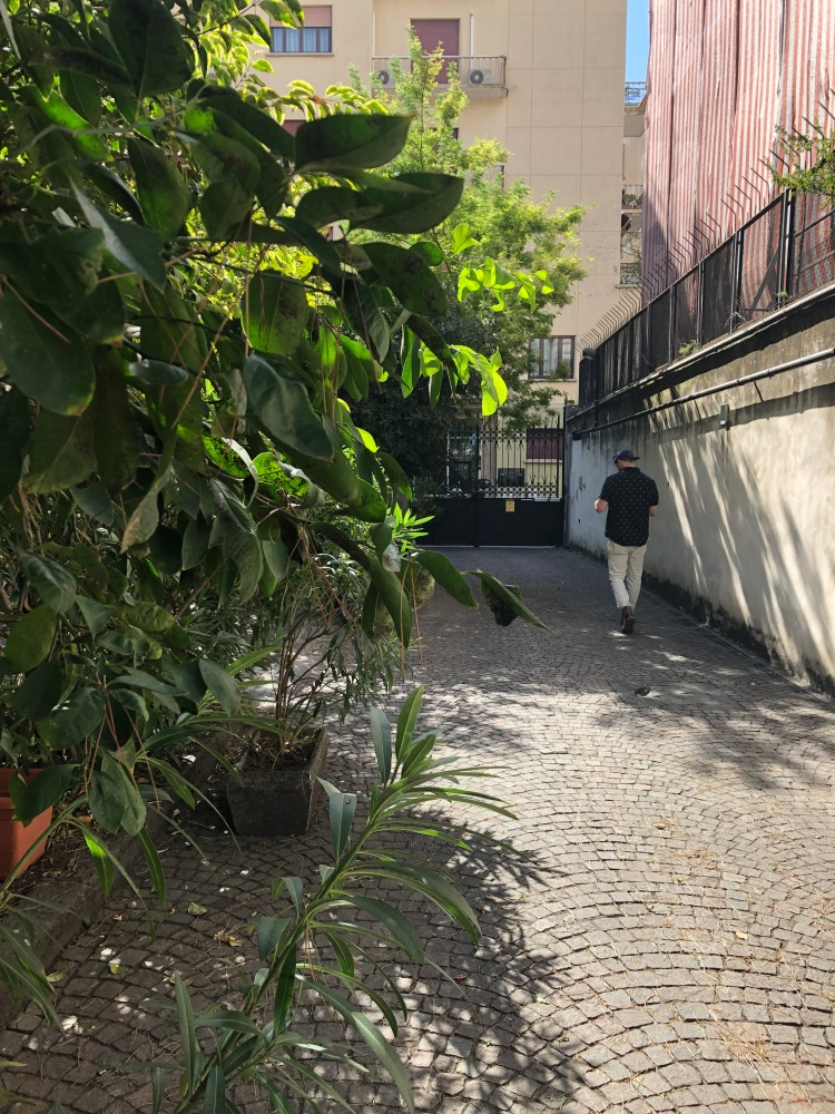 male walking down a pretty street on airbnb in naples italy