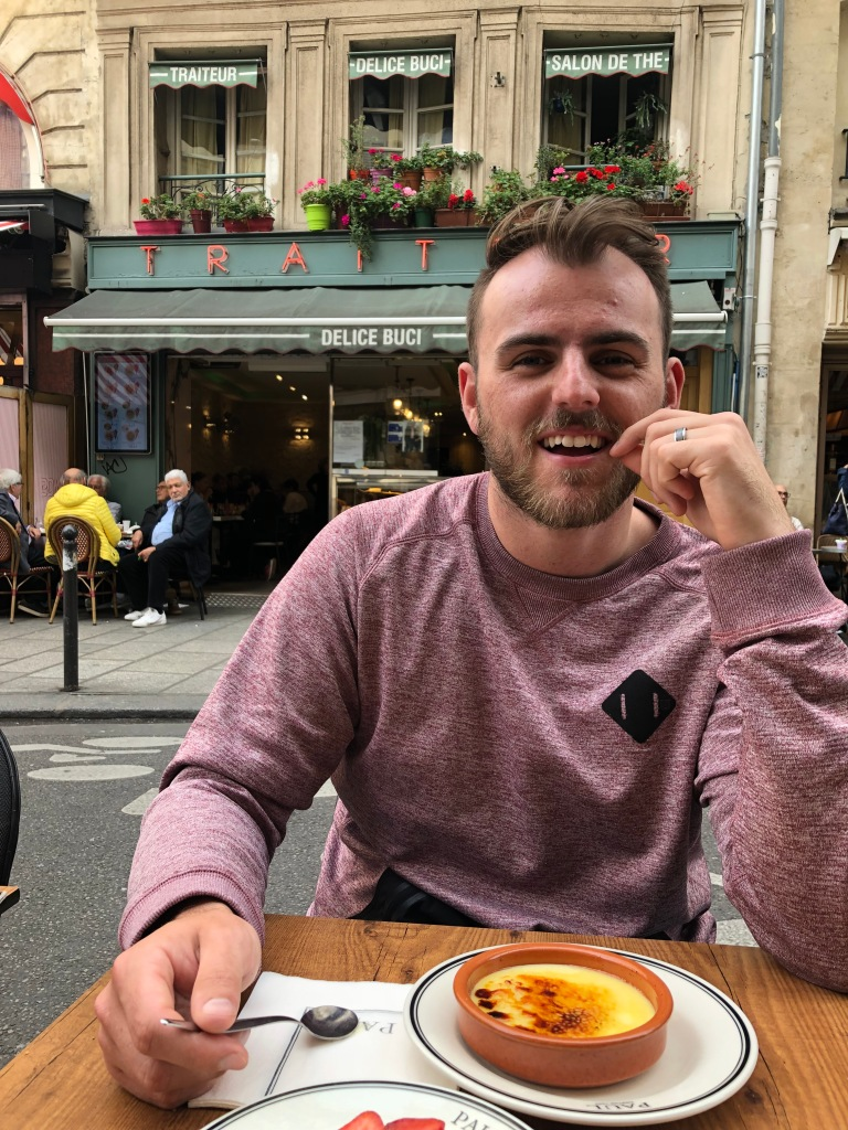 newlywed male eating creme bruelle at a cafe on rue de bucci in paris france