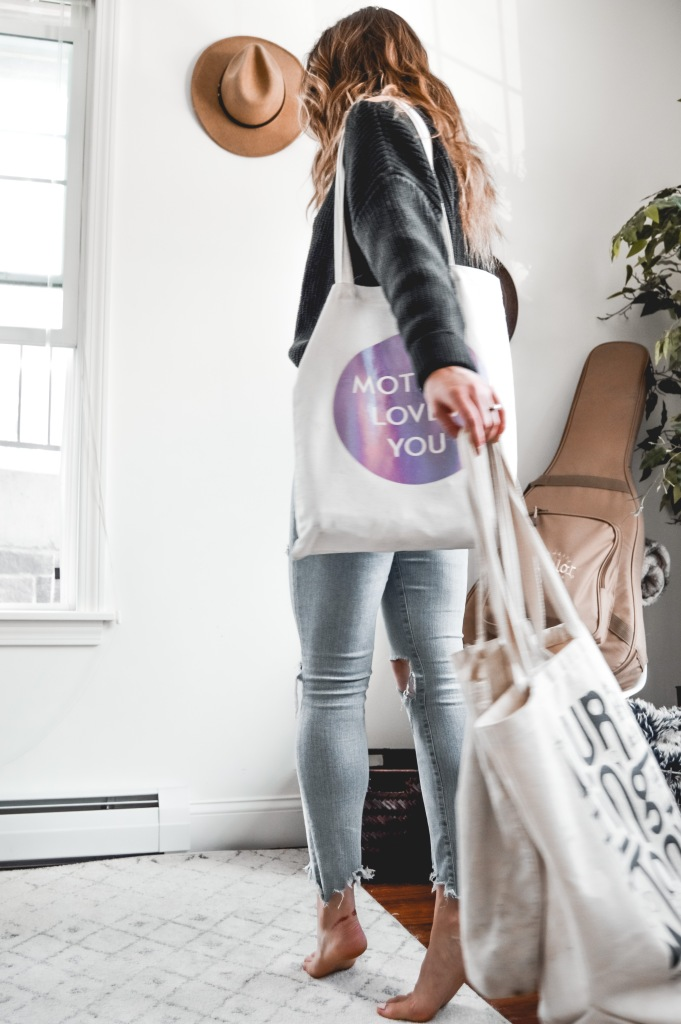 young woman in apartment wearing jeans and a black sweater holding reusable canvas bags