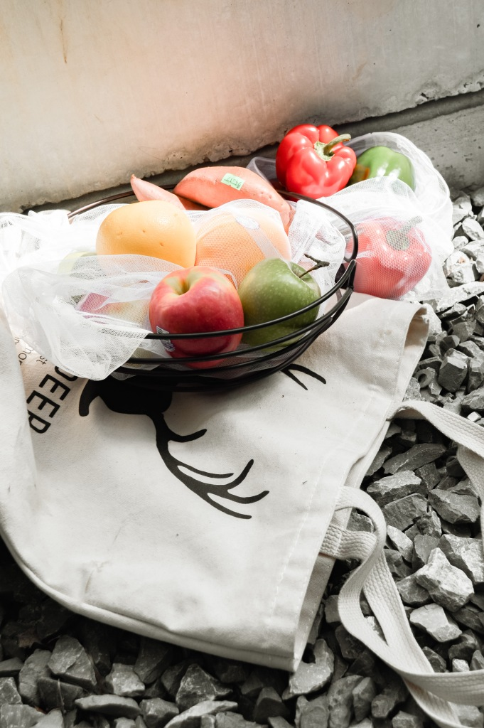 lots of produce like red and green apples grapefruit sweet potatoes and green and red bell peppers shown in reusable and sustainable produce bags on top of a canvas bag with deer antlers